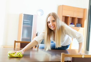 long-haired housewife cleaning table with rag