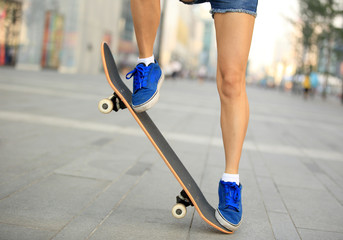 woman skateboarder legs jumping in city