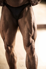 Bodybuilder showing his muscular thigh