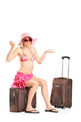 Uncertain female tourist sitting on her baggage