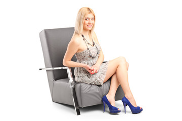 Fashionable woman sitting in a modern armchair