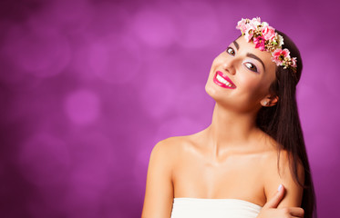 Brunette girl with wreath on violet background.