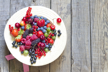 Summer wild berry fruits in the hat concept on vintage boards