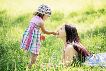 girl feeding her mother a blade of grass