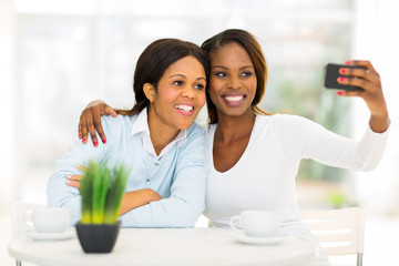 middle aged african mother and daughter taking self portrait