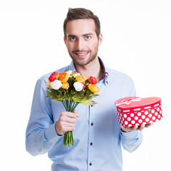 Happy handsome man with flowers a gift.