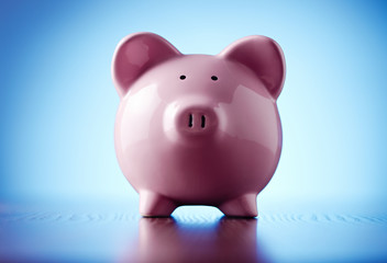 Pink ceramic piggy bank on blue