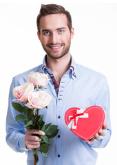 Young happy man with a pink roses and a gift.