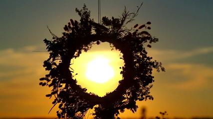 The sun shines through the wreath.