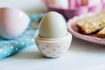 Blue duck egg in egg cup with pink hearts