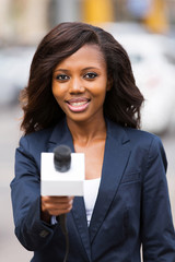 african news reporter interviewing with microphone