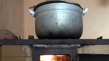 boiling old pot on retro poor fireplace in farm