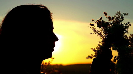 Portrait of a girl at sunset with a wreath of wildflowers.