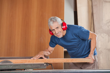 Happy Senior Carpenter Cutting Wood With Tablesaw