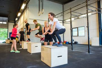 Athletes Doing Box Jumps At Gym