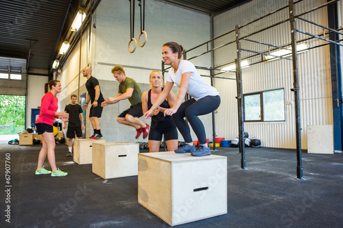 Fotobehang Gymnastiek Athletes Doing Box Jumps At Gym