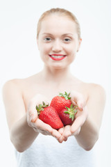Portrait of young attractive woman in towel with strawberry