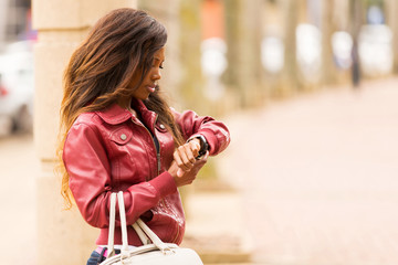 african woman looking at watch