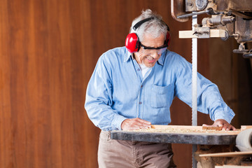 Carpenter Cutting Wood With Bandsaw