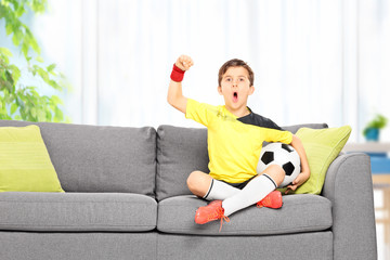 Little boy watching a football match at home