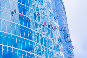 Washers wash the windows of modern skyscraper.