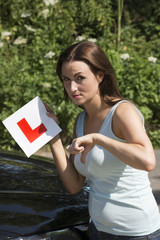 Woman driver holding L plate and thumbs down for a failure