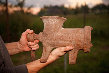 old rusty meat grinder in hands of the man