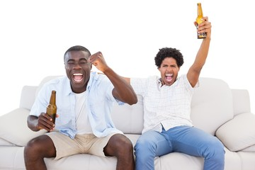 Ecstatic sports fans sitting on the couch with beers