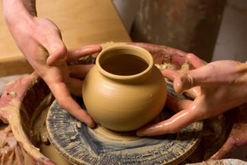 hands of a potter, creating an earthen jar