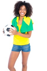 Pretty football fan with brazilian flag smiling at camera