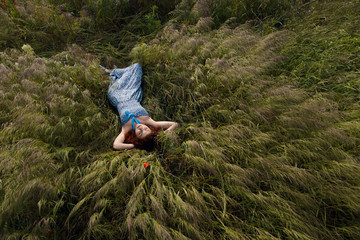 Beautiful woman sleeping on tall grass