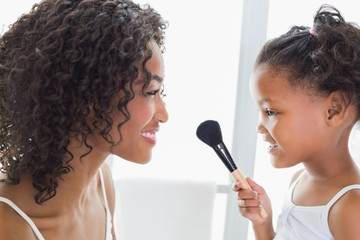 Pretty mother teaching her daughter about makeup