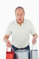 Mature man feeling buyers remorse holding bags
