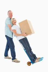 Fun older couple holding moving boxes