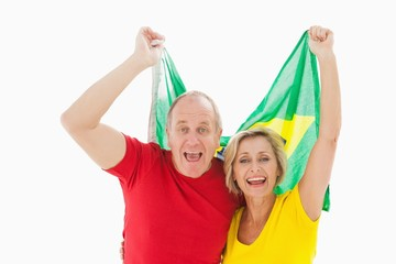Happy older couple cheering at camera holding brazil flag