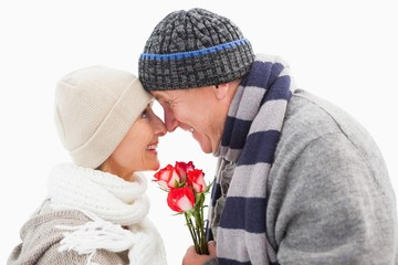 Happy mature couple in winter clothes with roses