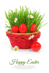 Wicker basket with red Easter eggs and fresh grass