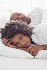 Upset woman lying in bed with sleeping boyfriend