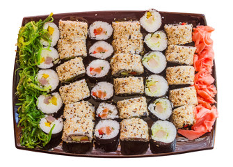 large plate with a wide selection of sushi, seaweed and ginger