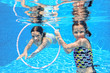 Happy active kids play underwater in swimming pool