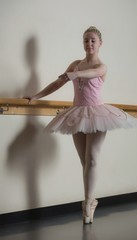 Beautiful ballerina standing en pointe holding barre