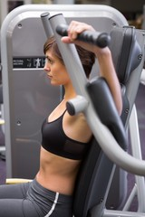 Athletic brunette using weights machine for arms