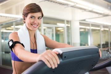 Fit brunette running on the treadmill listening to music