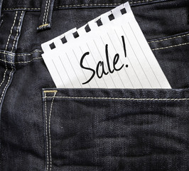 Sale! written on a peace of paper on a jeans background