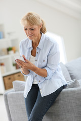 Senior woman sending text message with smartphone