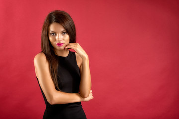 sexy brunette woman in black dress isolated on red background