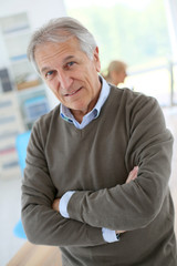 Smiling senior man sitting in office