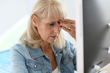 Senior woman in office having a headache