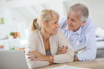 Senior couple at home filling pension paper