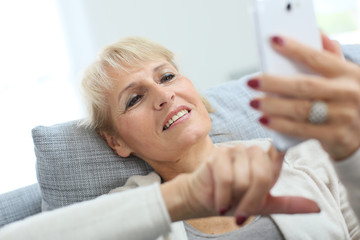 Senior woman reading message on smartphone